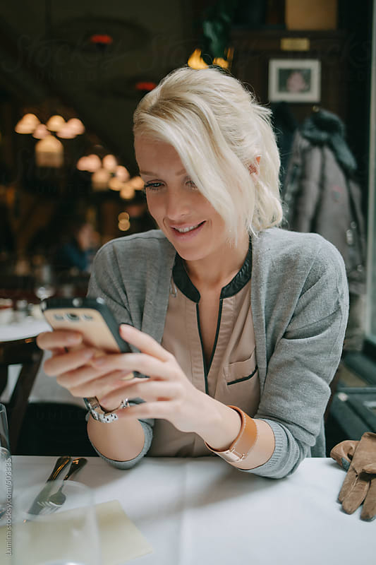 Happy Woman Texting at a Restaurant by Lumina for Stocksy United