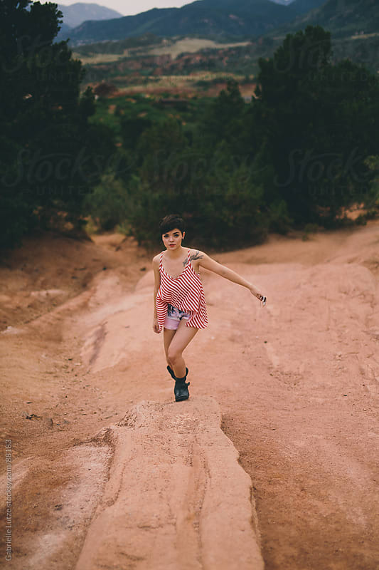 Edgy girl in striped shirt hiking outdoors by Gabrielle Lutze for Stocksy United