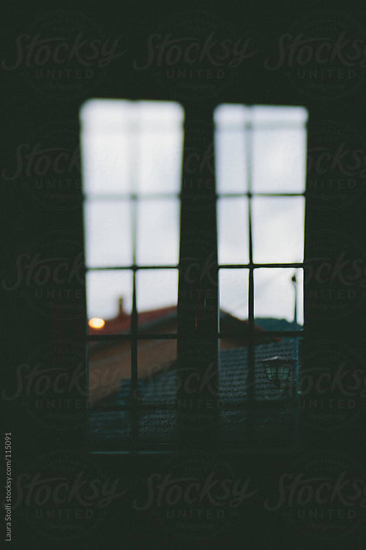 Blurred sight on italian mountain village through a window at dusk by Laura Stolfi for Stocksy United