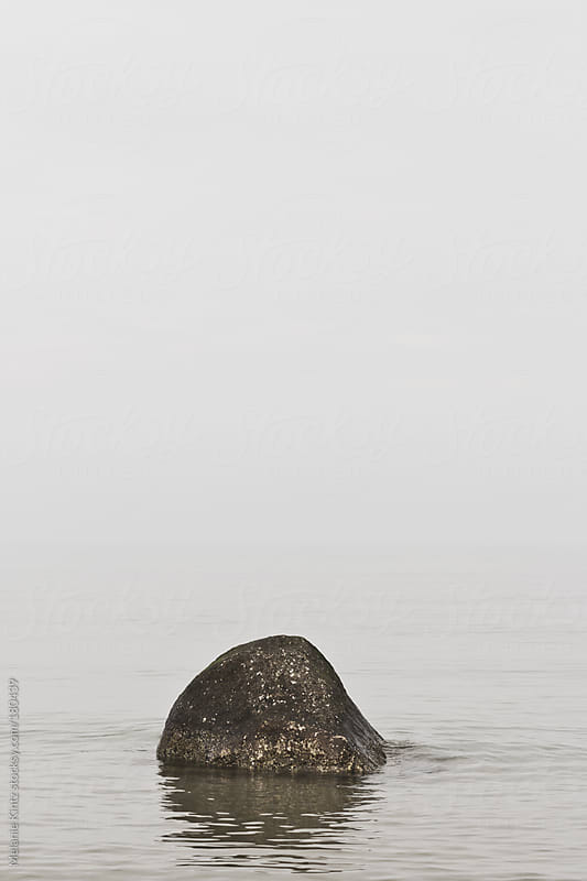 Rock in the sea on a foggy morning by Melanie Kintz for Stocksy United