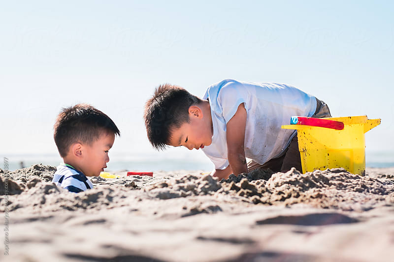 Asian boys having fun on the beach during summer by Suprijono Suharjoto for Stocksy United