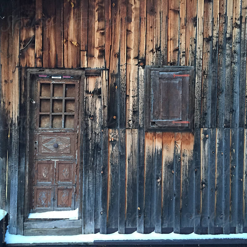 Old wooden barn with door and snow on the ground by Soren Egeberg for Stocksy United