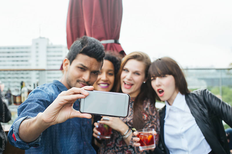 Cool Young Indian Man Taking Smartphone Selfie With Three Tipsy Women at Rooftop Bar by VISUALSPECTRUM for Stocksy United