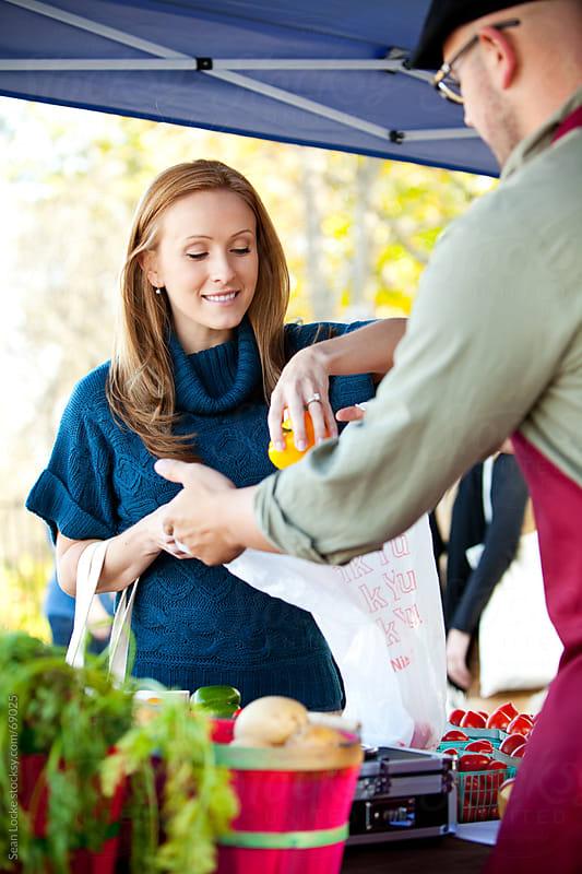 Farmer's Market: Seller Helps Woman Bag Produce by Sean Locke for Stocksy United