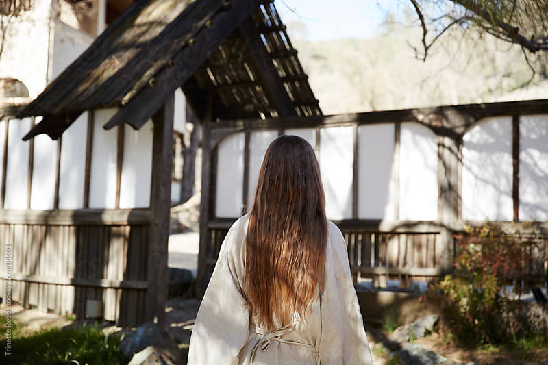 Woman in linen robe walking in front of entrance of Japanese spa by Trinette Reed for Stocksy United