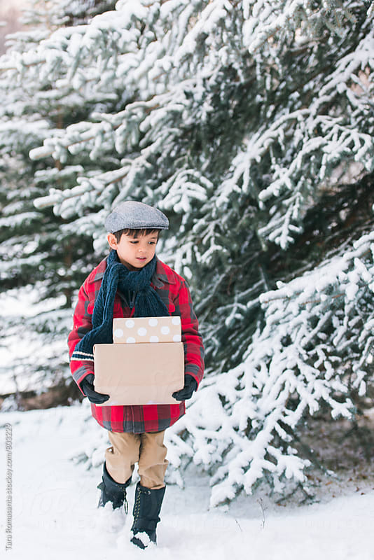child walking in the snow carrying gifts by Tara Romasanta for Stocksy United