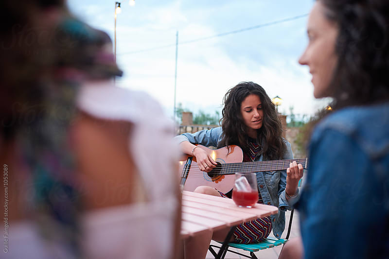 Brunette playing guitar at party outdoor by Guille Faingold for Stocksy United