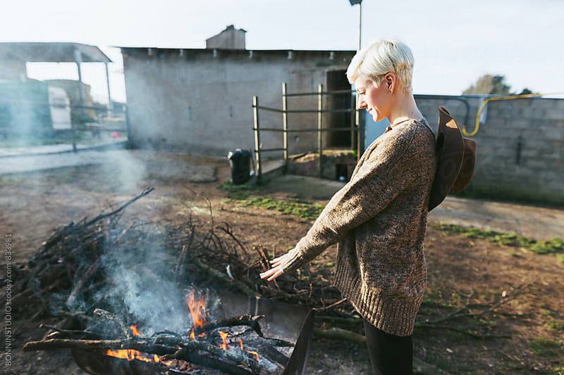 Woman farmer warming her hands over a bonfire on farm. by BONNINSTUDIO for Stocksy United