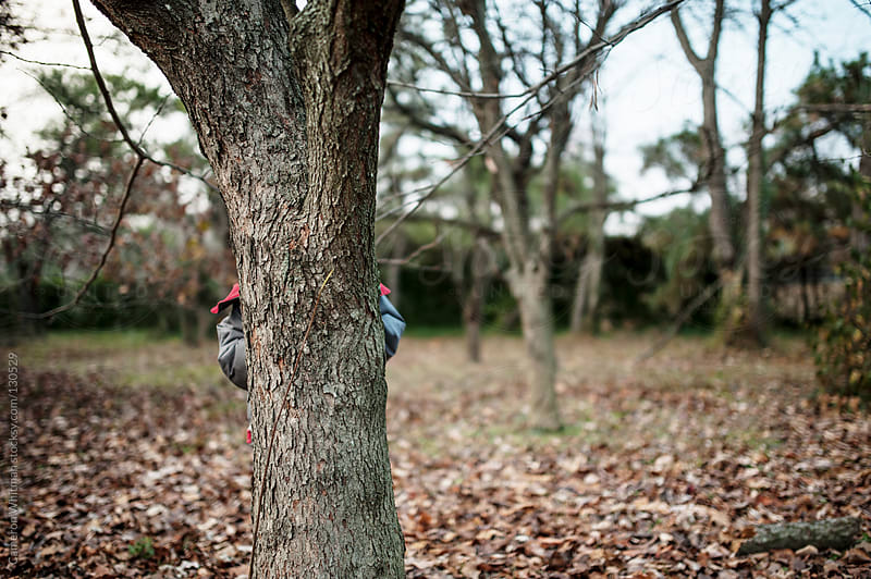 Boy Playing Hide And Seek Behind A Tree by Cameron Whitman for Stocksy United