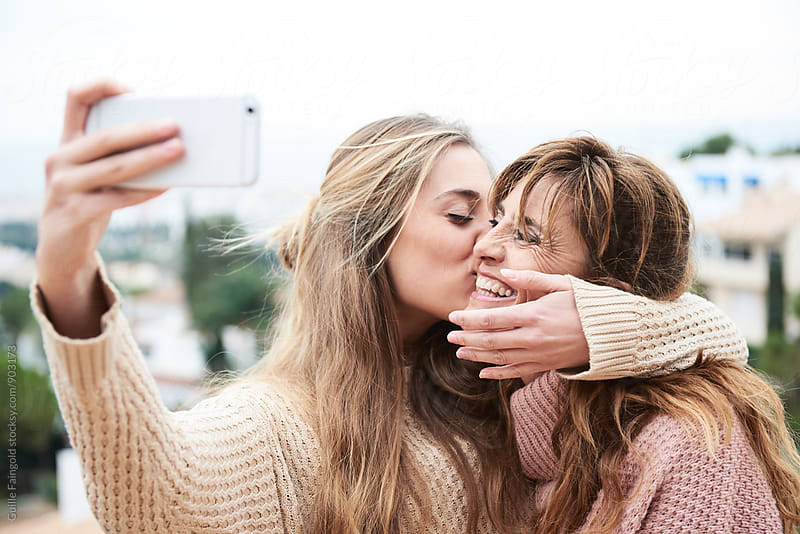 Woman kissing her mother while making selfie by Guille Faingold for Stocksy United