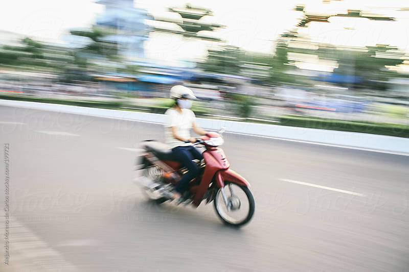 Young woman riding a motorbike - moped. Speed blurred image by Alejandro Moreno de Carlos for Stocksy United