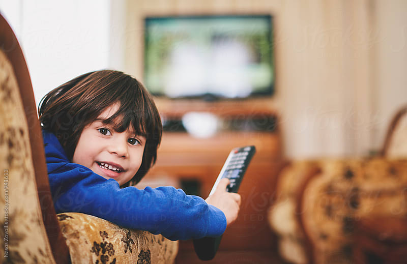 5 years old boy holding a tv remote control by Nasos Zovoilis for Stocksy United
