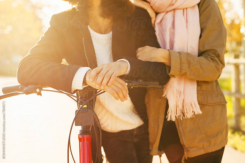 Closeup of couple standing together with their bicycle. by BONNINSTUDIO for Stocksy United
