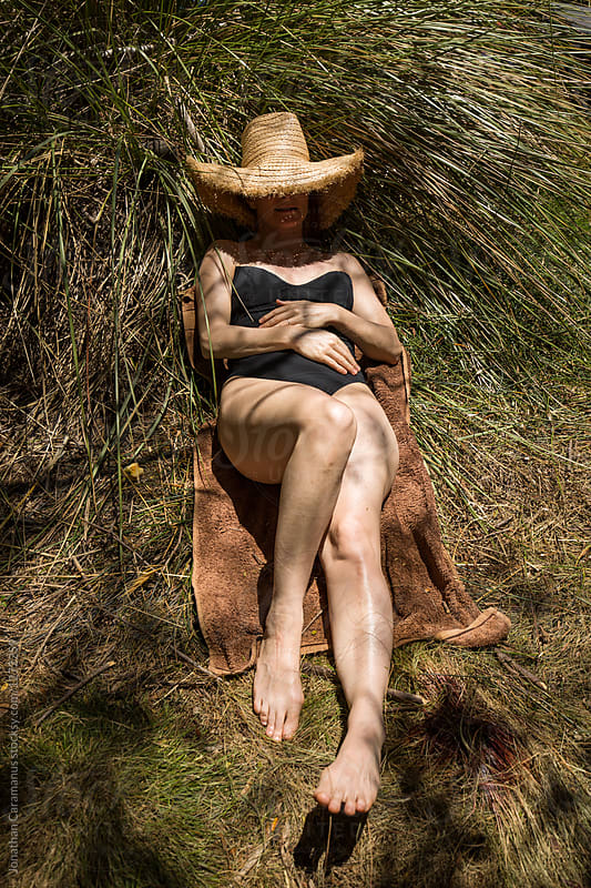 Woman lying relaxed in the grass in the sun wearing a straw hat