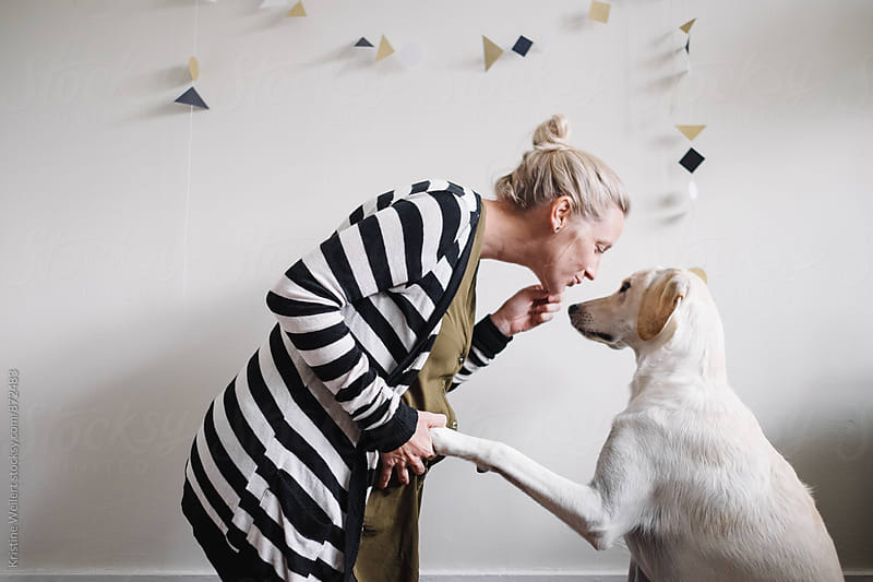 Pregnant woman kissing her white dog by Kristine Weilert for Stocksy United