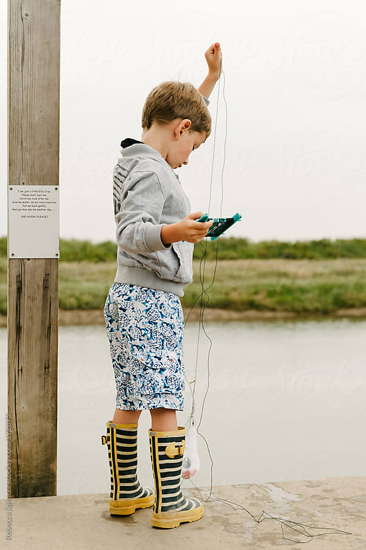 Young boy pulling up fishing line to check for crabs.  by Rebecca Spencer for Stocksy United