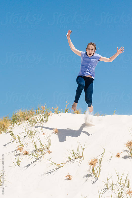 teen girl jumping the sand dunes by Gillian Vann for Stocksy United