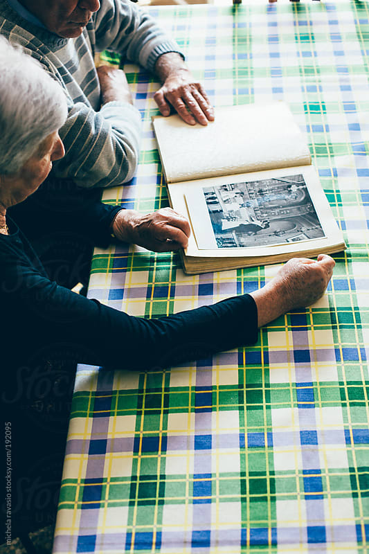 Elderly couple looking at their wedding album  by michela ravasio for Stocksy United