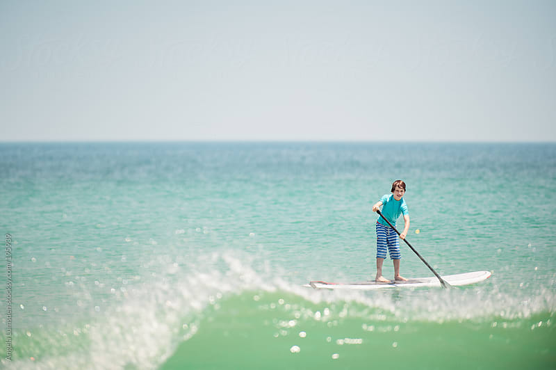Boy on a stand up paddle board at the beach by Angela Lumsden for Stocksy United