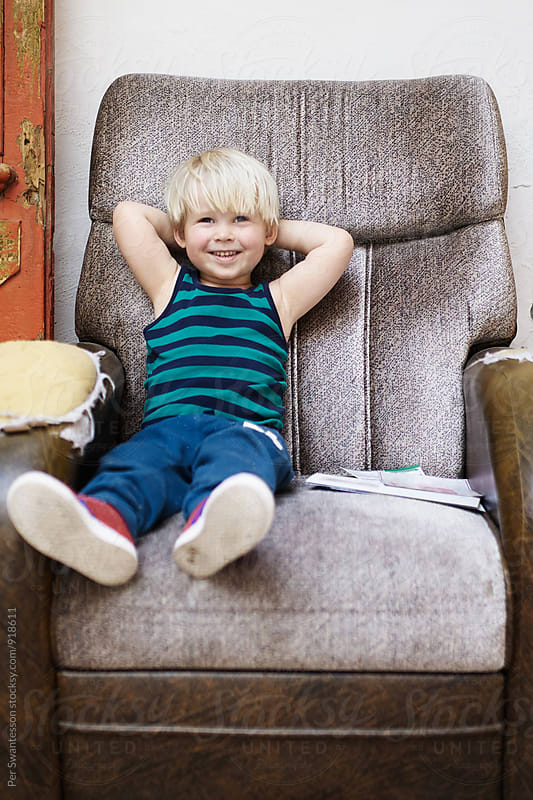 Cute smiling confident toddler in an old armchair by Per Swantesson for Stocksy United