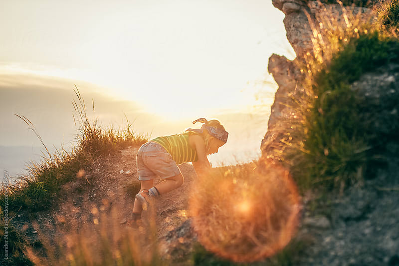 young boy with headband climbing up a mountain at sunset in autumn by Leander Nardin for Stocksy United