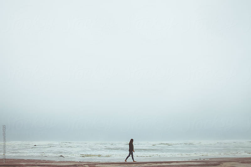Woman walking on a misty beach by Micky Wiswedel for Stocksy United