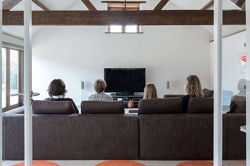 Rear view of family watching television. Modern living room. by Paul Phillips for Stocksy United