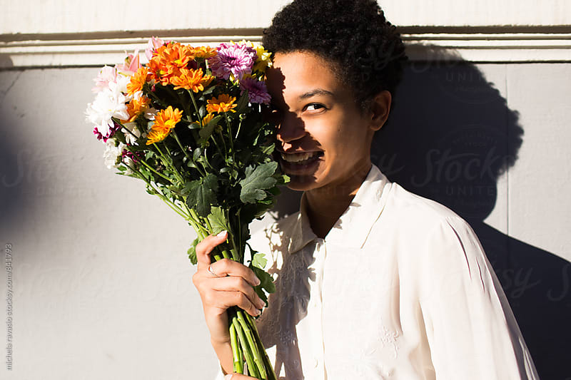 Smiling woman holding a bouquet of flowers by michela ravasio for Stocksy United
