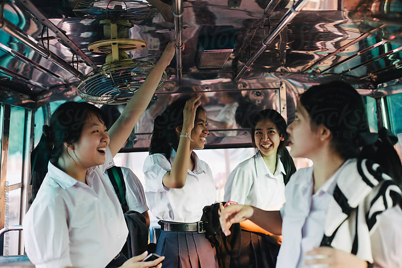 High school students in uniform on the bus after school by Nabi Tang for Stocksy United