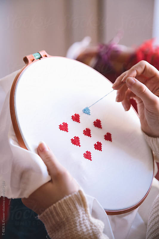 Close-up of woman's hands doing embroidery.Valentine's day by T-REX & Flower for Stocksy United