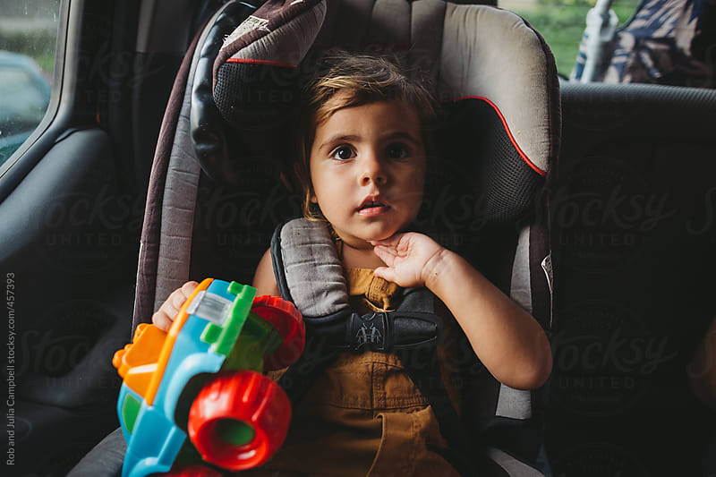 Cute young toddler girl sitting in carseat by Rob and Julia Campbell for Stocksy United