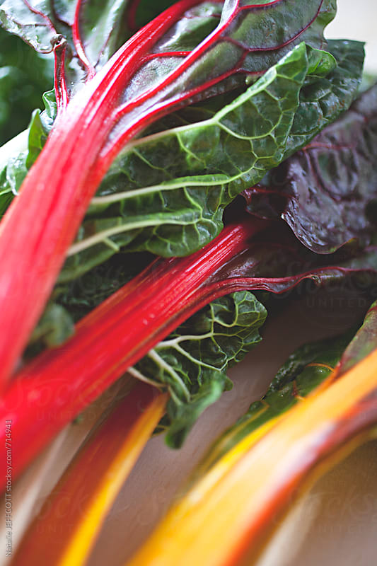 Rainbow silverbeet / spinach / chard on table top by Natalie JEFFCOTT for Stocksy United