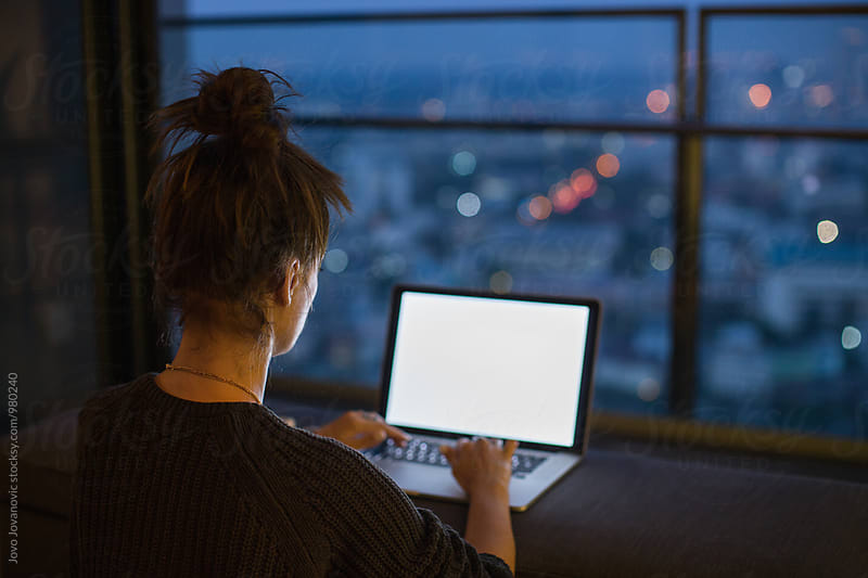 Woman working from her laptop at night  by Jovo Jovanovic for Stocksy United
