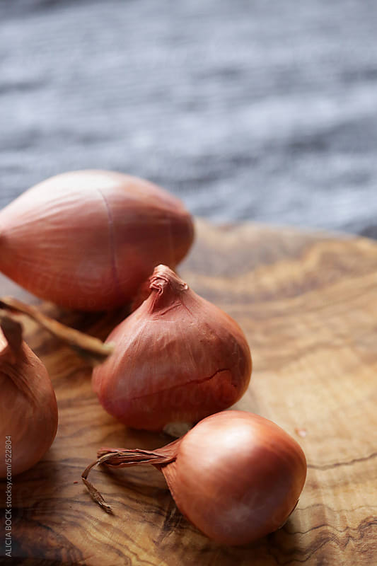 Organic Shallots On A Wood Cutting Board by ALICIA BOCK for Stocksy United