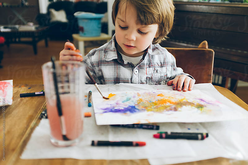 Young boy learning to paint with watercolor crayons by Cameron Whitman for Stocksy United