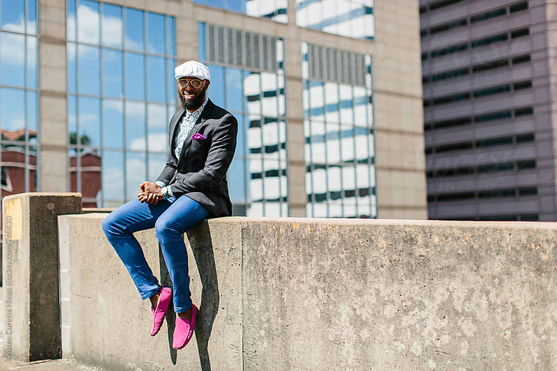 A handsome young male wearing stylish attire sitting outdoors in the city by Kristen Curette Hines for Stocksy United