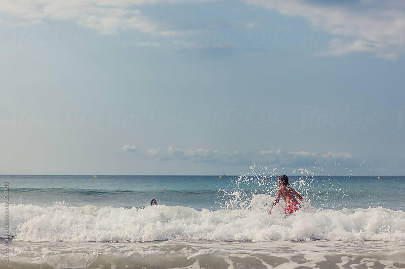 Kids playing in the ocean crashing against the waves in the summer by Cindy Prins for Stocksy United