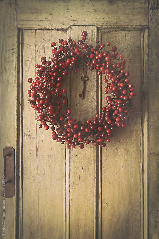 Berry wreath hanging on old wood door by Sandra Cunningham for Stocksy United