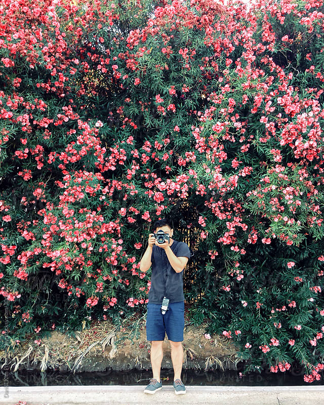 Young man taking picture in front of flower wall by Daniel Kim Photography for Stocksy United