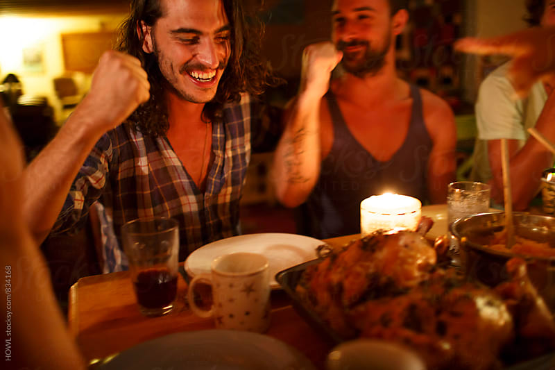 Friends sit around laughing and enjoying a dinner in candlelight.  by HOWL for Stocksy United