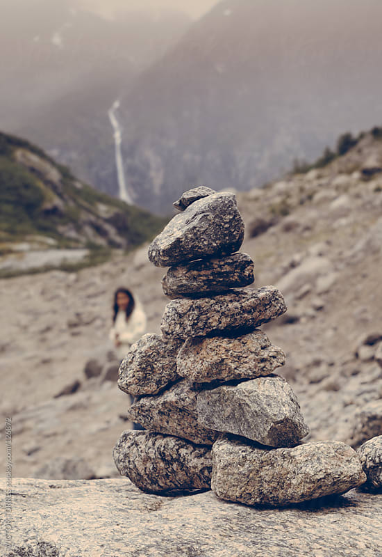 Woman Behind a Stack of Stones by VICTOR TORRES for Stocksy United