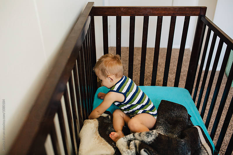 Toddler boy in a striped shirt in a dark brown crib. by Jessica Byrum for Stocksy United