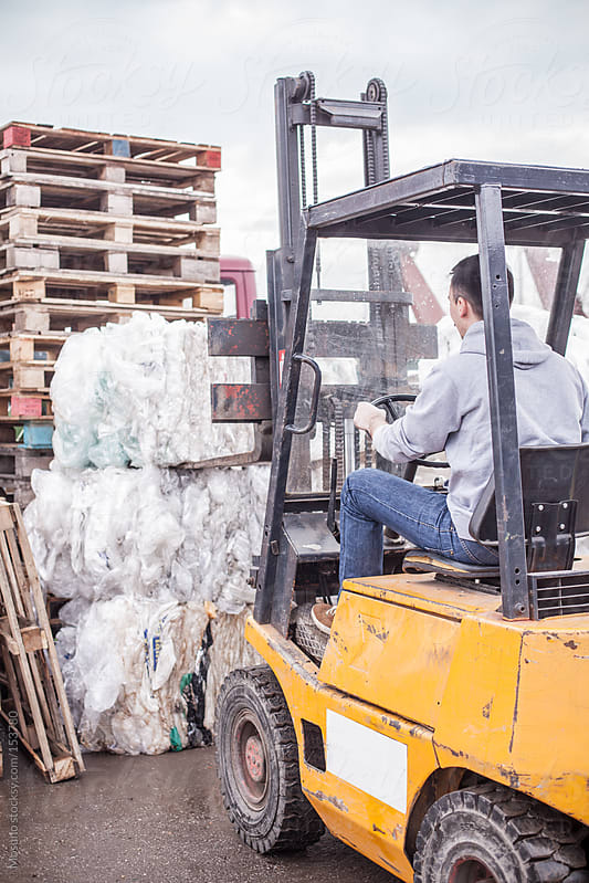 Man Working on a Forklift in Recycle Factory by Mosuno for Stocksy United