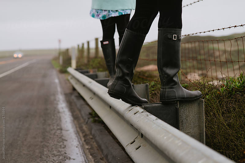 young women stand on guard rail on side of road in california by Jesse Morrow for Stocksy United