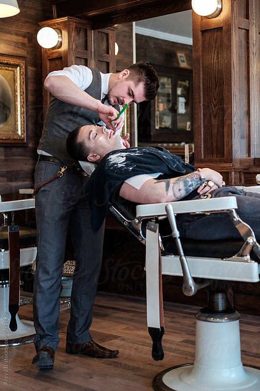 A gentleman barber finishes a classic straight razor shave on a client. by Riley J.B. for Stocksy United