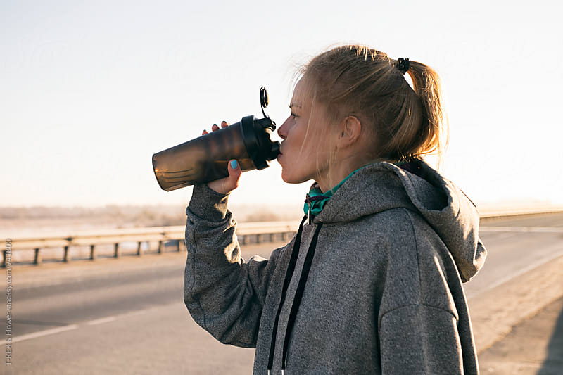 Sportswoman drinking from mug on road by Danil Nevsky for Stocksy United