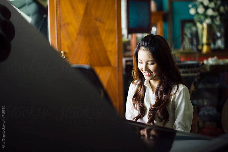 Woman smiling, sitting at piano by Alita Ong for Stocksy United