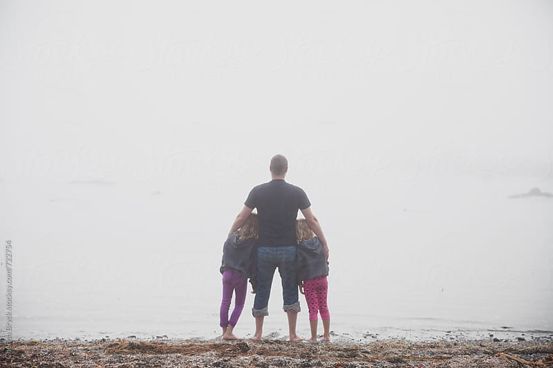 Father and daughters embrace at beach. by Cherish Bryck for Stocksy United
