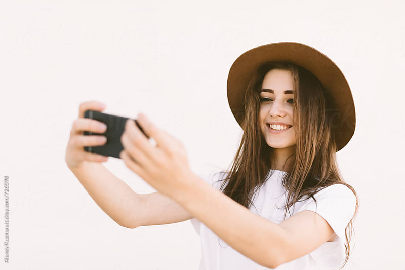 happy woman taking a selfie by Alexey Kuzma for Stocksy United
