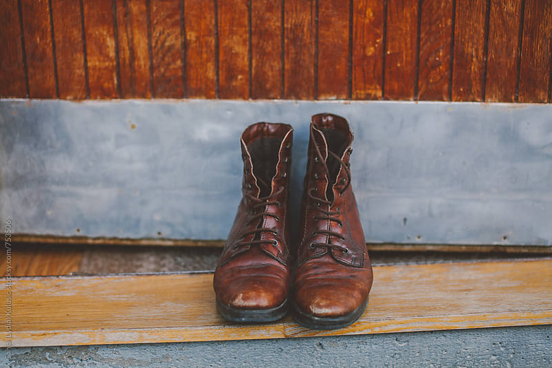 Vinage brown laced  up boots in front of old doors by Sanja (Lydia) Kulusic for Stocksy United